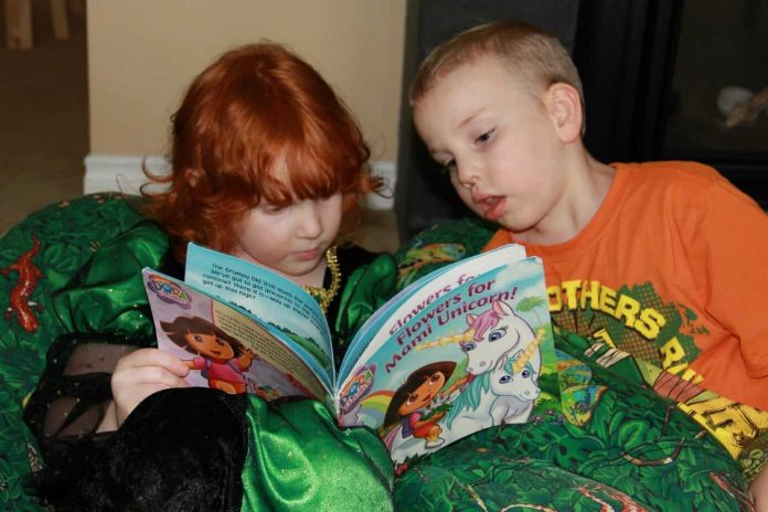 Our daughter Evey reading a Dora the Explorer book to her brother Gabe. Both children are homeschooled and Gabriel lives with autism.