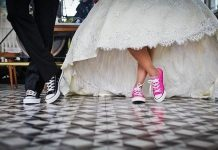 bride and groom seen from the kness down only with both wearing colorful converse shoes
