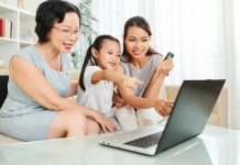 Family sitting on the sofa online shopping