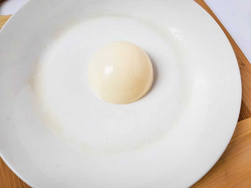 a half-sphere of white chocolate with the open side face down on a plate