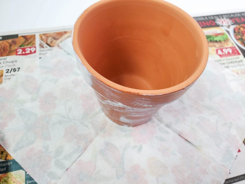The second step in creating a decoupage flower pot. A terracotta flower pot standing at the center of an unfolded, face down paper napkin.