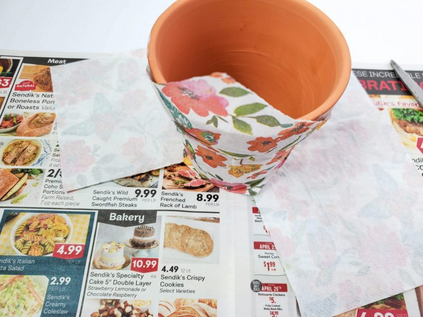 Decoupage flower pot part way through creation. A paper napkin is smoothed against the outside and the tip of the napkin is folded against the rim.