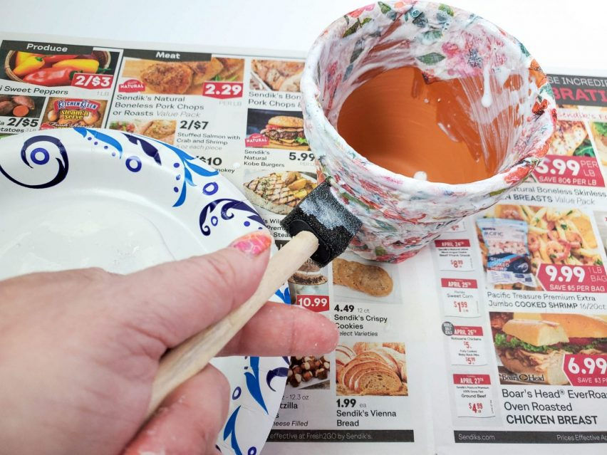 Decoupage flower pot craft step one. Applying a layer of Mod Podge to the outside surface of a flower pot, using a foam brush.