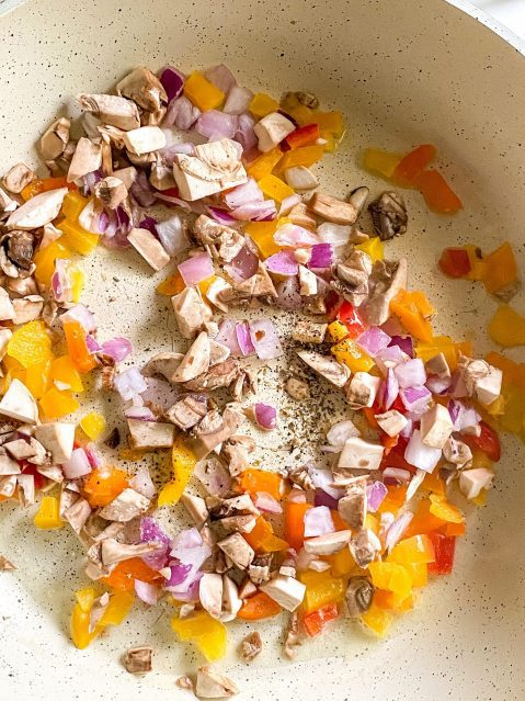 raw, diced red, orange and yellow peppers and red onion on the bottom of a ceramic frying pan.